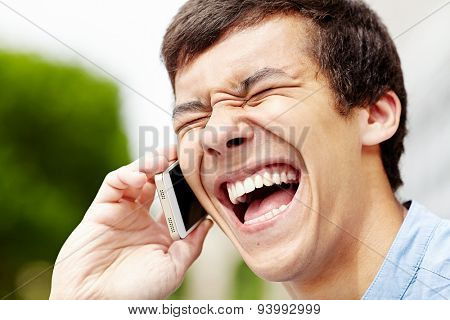 Closeup portrait of laughing young man with closed eyes and wide open mouth talking on mobile phone outdoor