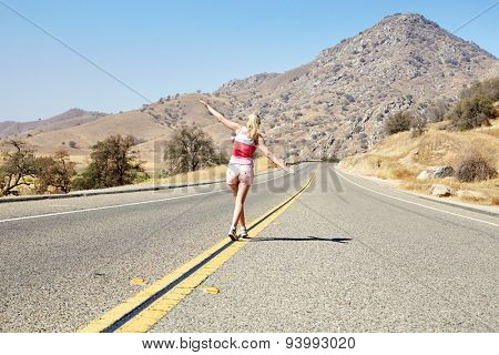 Rear view of young woman with outstretched arms walking along yellow dividing line of empty road among arid landscape