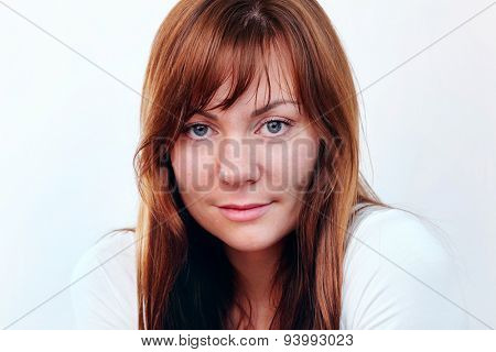 Close up portrait of charming young woman with long ginger hair, forelock and big gray eyes over white background