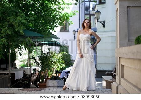 Full length portrait of beautiful model woman in white dress posing summer street
