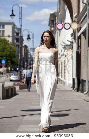 Full length portrait of beautiful model woman walking in white dress in summer street