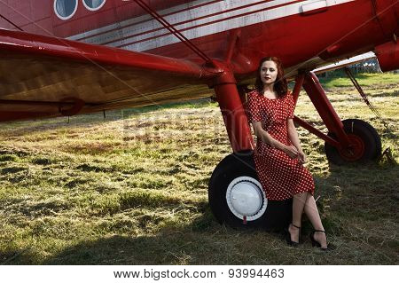 pin-up female sitting on plane wheel in red dress