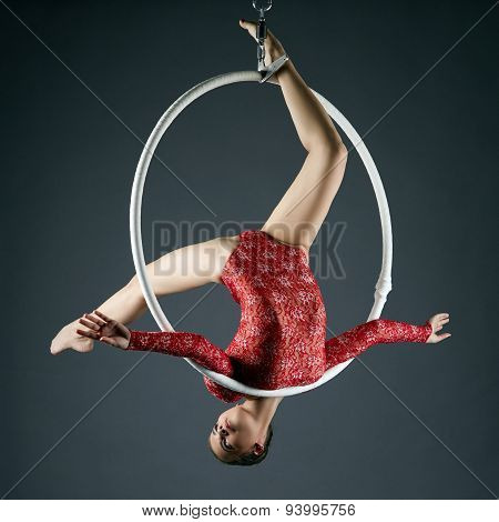Lovely gymnast performs acrobatic stunt on hoop