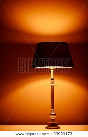 interior lamp with warm light against plaster wall background