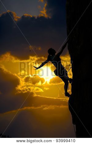 Female climber silhouette and sunset cloud sky