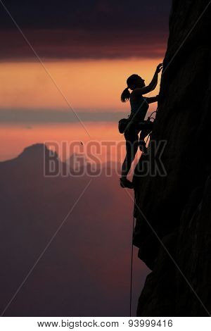 Climber silhouette on mountain sunset background