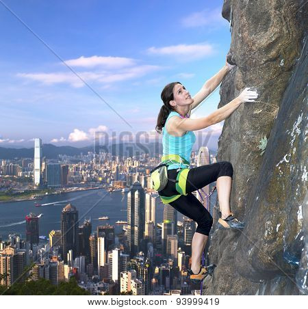 Female rock climber over the city skyline