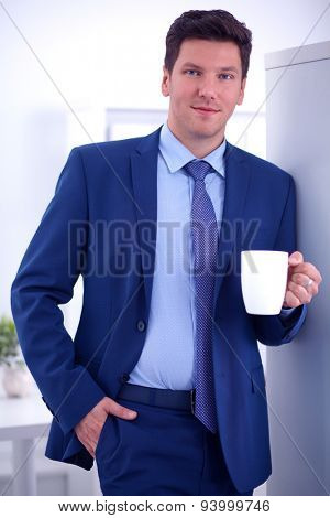 Smiling businessman standing with cup of coffee .