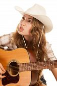 stock photo of cowgirl  - Sesy cowgirl in cowboy hat with a nylon string acoustic guitar - JPG