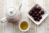 pic of teapot  - fresh healthy hot tea in a teapot and cup whit cherries - JPG