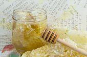 stock photo of decoupage  - Honeycomb dipper and lemon close up on a handmade decoupage table - JPG