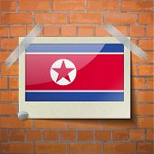 stock photo of north star  - Flags of Korea North scotch taped to a red brick wall - JPG