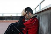 image of sob  - downcast young guy looking down with hands on forehead - JPG