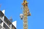 foto of mixer  - Crane lifting concrete mixer container against blue sky - JPG