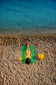 foto of top-hat  - Woman in swimsuit and hat lying on the green towel on the beach - JPG