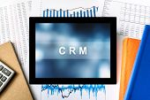 image of customer relationship management  - CRM or Customer relationship management word on tablet with financial graph background - JPG