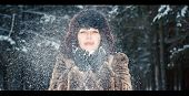 picture of girl walking away  - Girl blows away the snow from - JPG