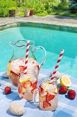 image of jug  - Ice cold homemade strawberry lemonade in jug and glasses with paper straws on outdoor summer pool side table plus copy space - JPG