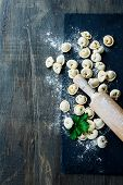 picture of italian parsley  - Homemade raw Italian ravioli and parsley on dark vintage background - JPG