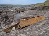 picture of sloop  - Boat wreckage upon cliff seascape photographed at Polzeath in Cornwall - JPG