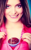 picture of mood  - sweet food or sex for brighten moods. Smiling woman having fun holds chocolate muffin cake on her chest blue background