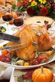 pic of kumquat  - Carving roasted turkey on a server tray garnished with fresh figs grape kumquat and herbs on fall harvest table - JPG
