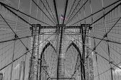 picture of brooklyn bridge  - A view of the arches of Brooklyn Bridge in NYC with the bridge sky and city in black and white but the USA flag in color - JPG