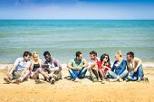 image of mans-best-friend  - roup of international best friends sitting at beach talking with each other  - JPG