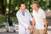 pic of crutch  - Cheerful doctor encouraging his patient to walk with crutches - JPG