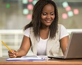stock photo of coworkers  - Attractive african woman sitting at the table in coworking centre and using laptop - JPG