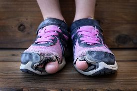 pic of human toe  - Detailed photo of shoes with holes in them and toes sticking out child kid young - JPG