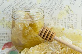 stock photo of decoupage  - Honeycomb dipper and lemon close up on a handmade decoupage table - JPG