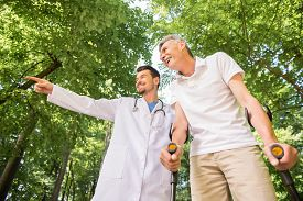 picture of crutch  - Cheerful doctor encouraging his patient to walk with crutches - JPG