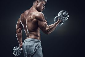 foto of shoulder muscle  - Handsome power athletic man in training pumping up muscles with dumbbells - JPG