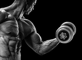 stock photo of shoulder muscle  - Handsome power athletic man in training pumping up muscles with dumbbell - JPG