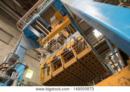 Brickyard. Bottom view of production machine with bricks