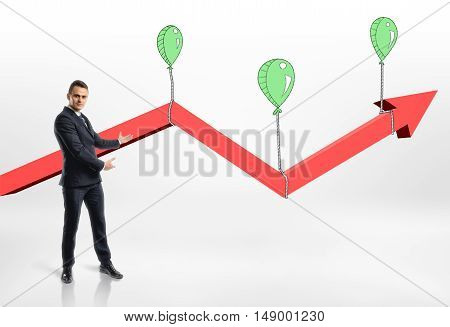 Businessman presents growing red arrow with air balloons. Targeting success and happiness. Success and development. Prosperous business.