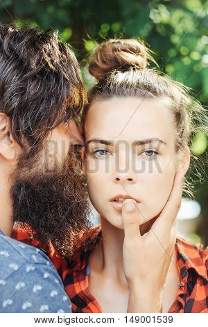 Young couple bearded handsome man hipster boyfriend hugging by hand pretty face of sexy girlfriend on green tree background