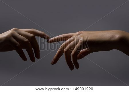 Two female young hands with perfect skin reaching out to one another connecting finger studio on dark background