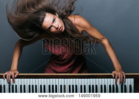 young girl or woman with pretty face and long brunette hair has sexy body posing near old retro wooden piano with keyboard on grey background