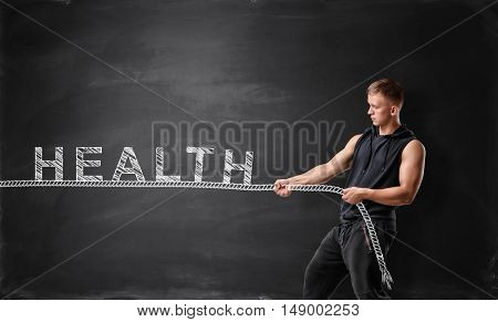 Muscular man pulls the rope with the word 'health'. Fitness and sport. Healthy lifestyle.
