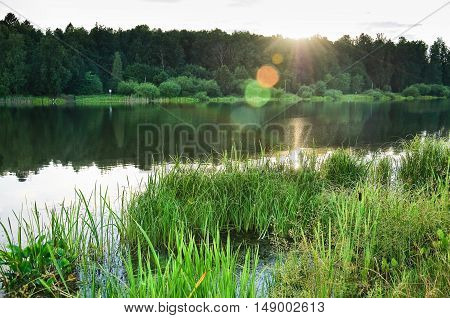Large Long (Vynohradiv) pond in the North of Moscow in the backlight of the evening sun