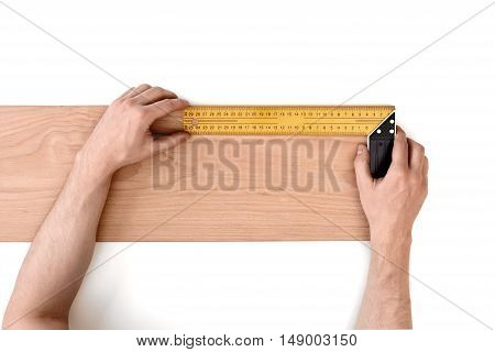 Close up view of a man's hands measuring wooden plank with a iron ruler, isolated on white background. Measurement. Building and maintenance. Handyman.
