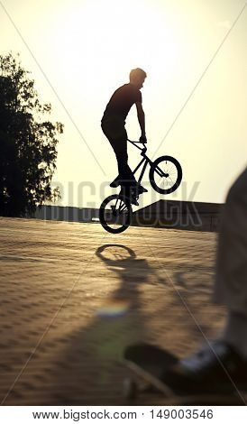 teenager jump on a bicycle outdoors, boy on skateboard, urban style
