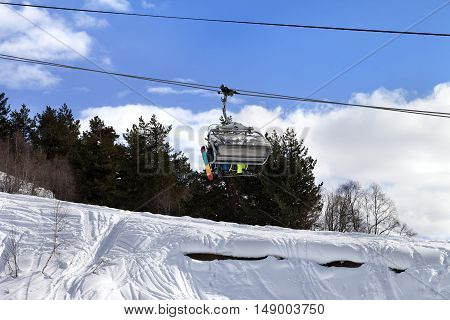 Skiers And Snowboarders On Chair-lift In Winter Mountain