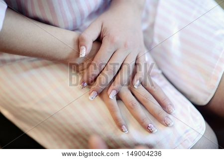 Hands of beautiful bride in white dressing gown. Beauty model girl in wedding robe. Female portrait with manicure. Close-up woman's arms. Cute lady indoors