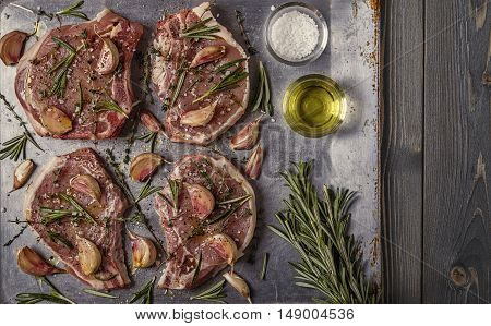 Raw pork chops with spices on a metal baking sheet top view.