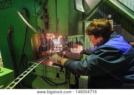 Tyumen, Russia - September 7, 2010: JSC Tyumenskie Motorostroiteli. Plant on production and repair of aviation engines. Senior woman operates metalworking machine