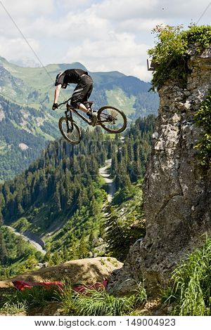 Extreme freeride mountainbiker jumping from a rock