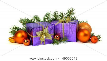 Close up orange New Year's spheres violet gift boxes and fur-tree branches isolated on a white background.